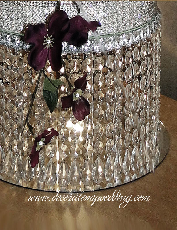 This elegant wedding cake stand is made with octagon bead strands and hanging teardrops.