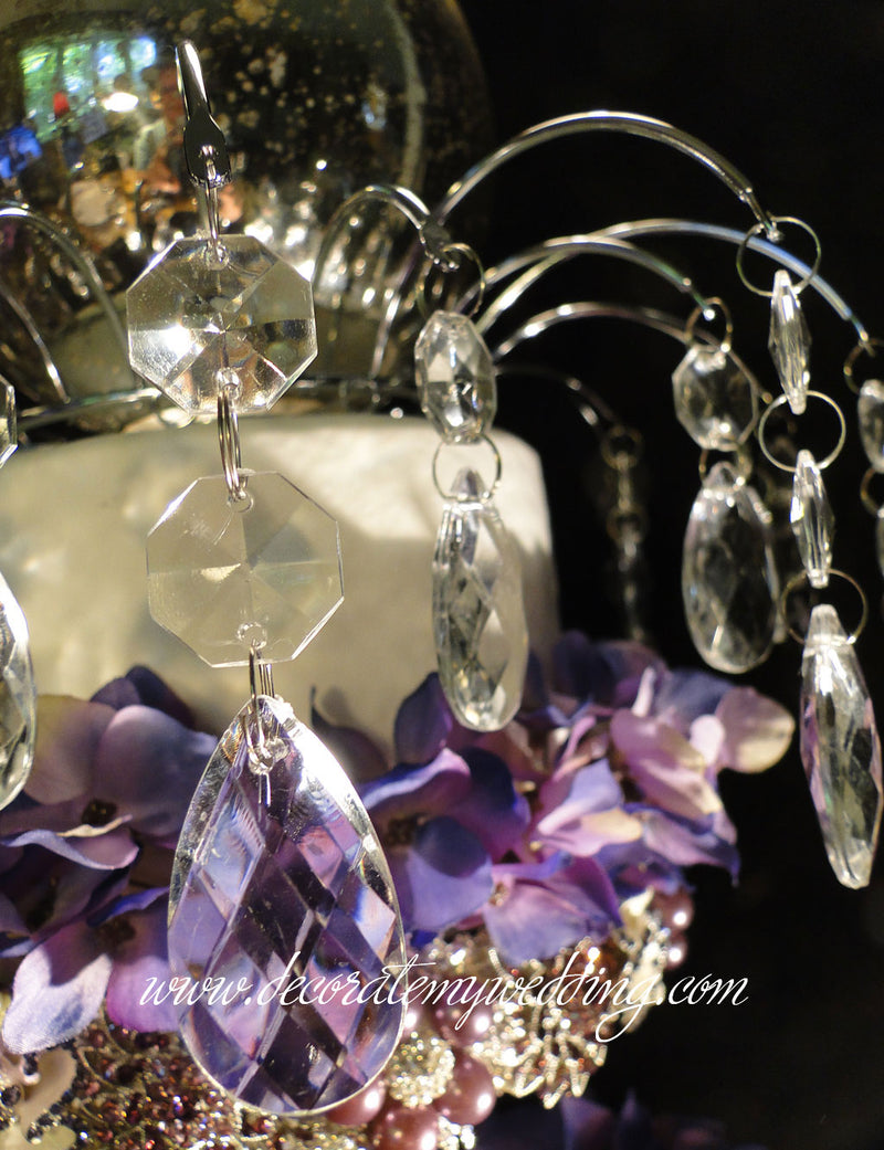 A close up look at an elegant wedding cake topper made with crystal beads and dangling teardrops.