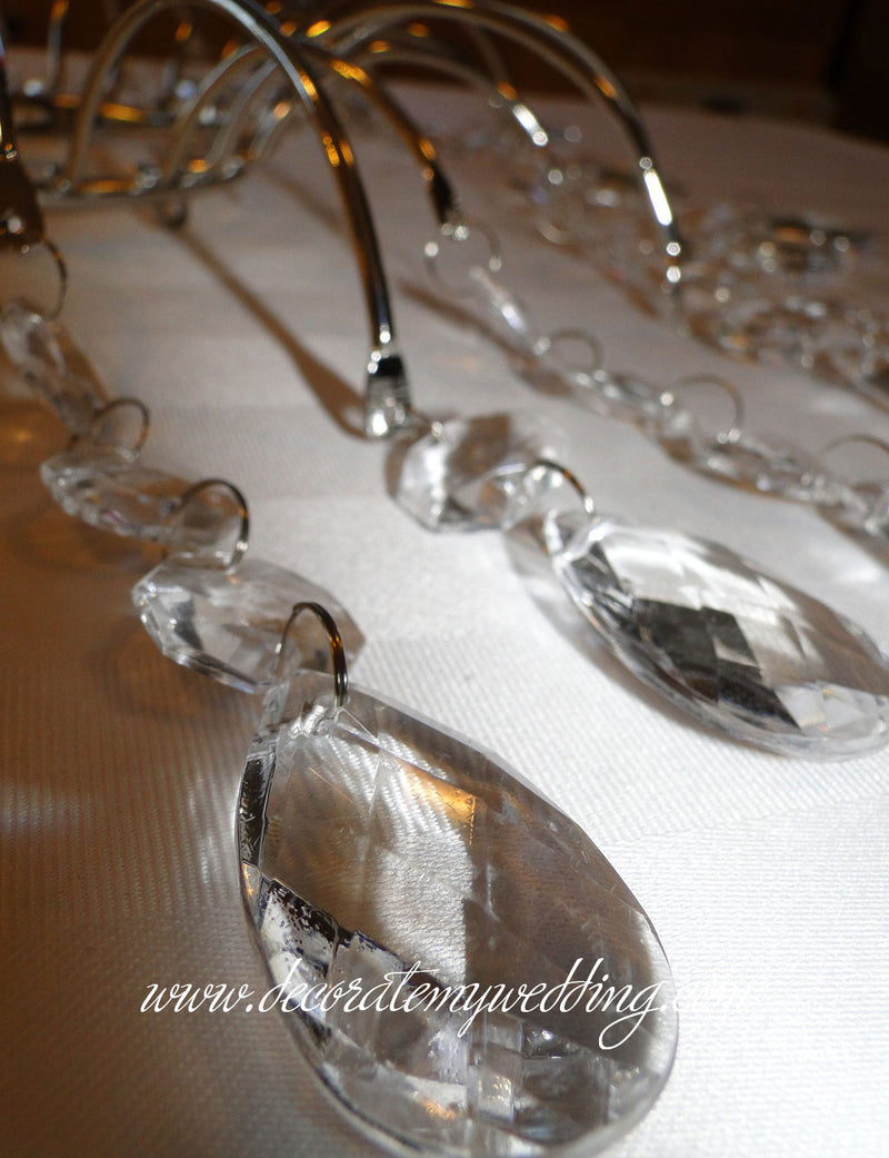 A close up look at the acrylic teardrops used to make this wedding cake topper.