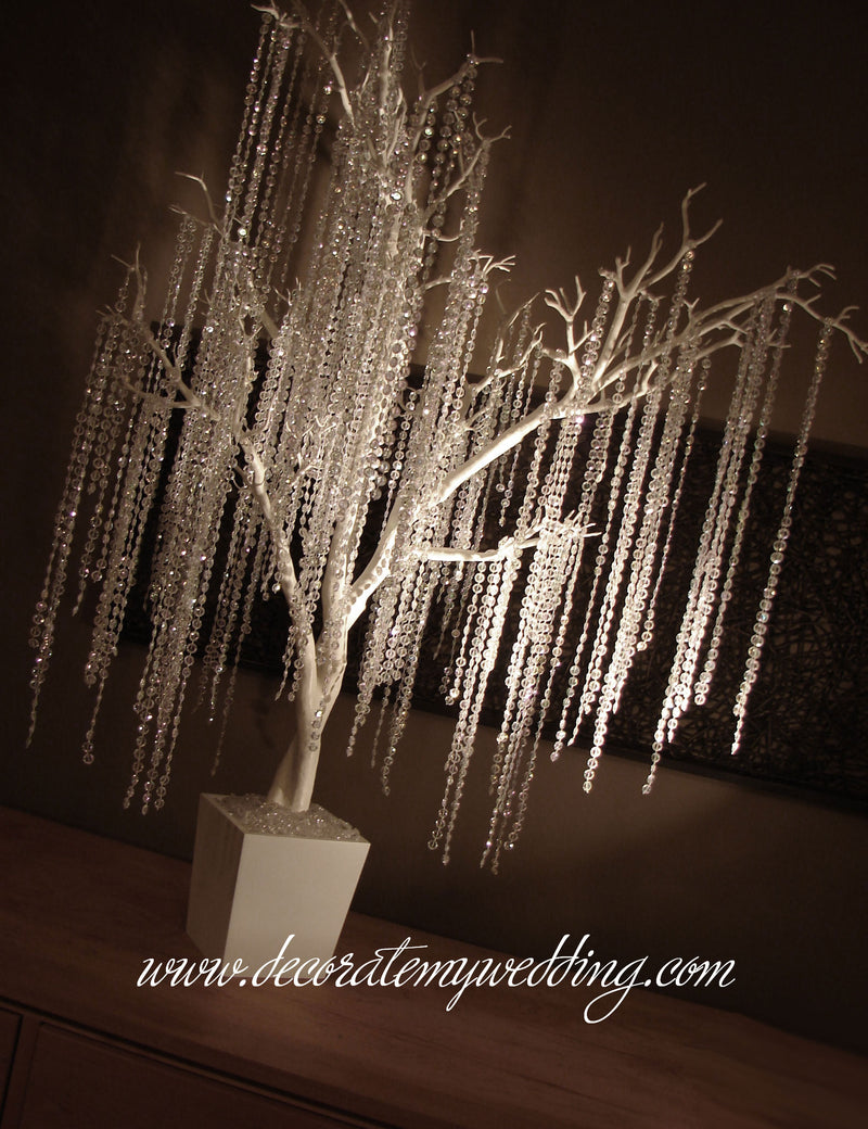 White faux tree decorated with white iridescent bead strands.
