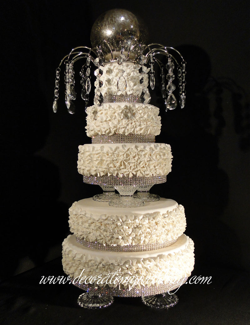Full view of five cake layers stacked on top of the footed cake stand.