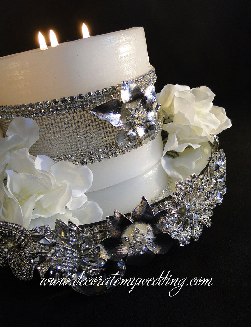 Footed candle holder with rhinestone brooches displays a white pillar candle and silk gardenia blooms.