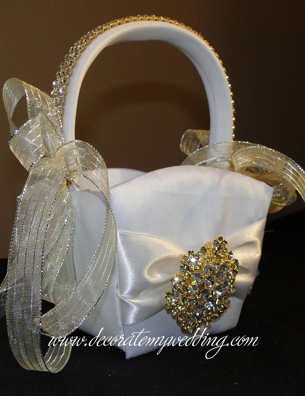 Gold flower girl basket trimmed with gold rhinestone banding, ribbons, and brooch.