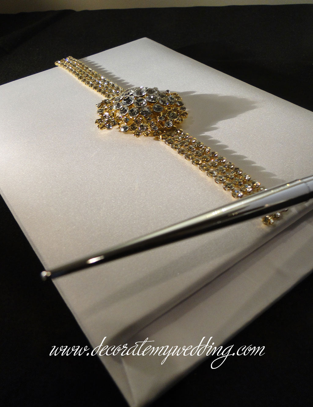 Gold guest book trimmed with rhinestone banding and a gold brooch.