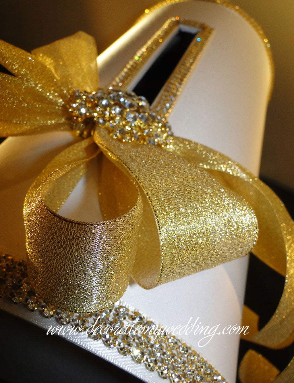 Gold wedding card box trimmed with gold rhinestone banding and ribbon.