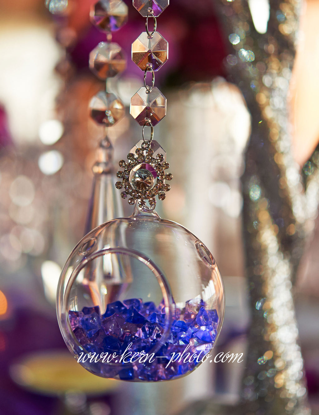 Clear bubble-shaped, hanging candle holder is filled with acrylic purple pebbles and accented with a rhinestone mini brooch.