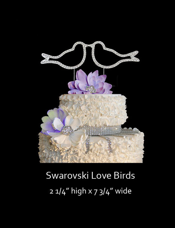 The love birds cake topper is made with Swarovski rhinestones and stand on the top of a wedding cake kissing.