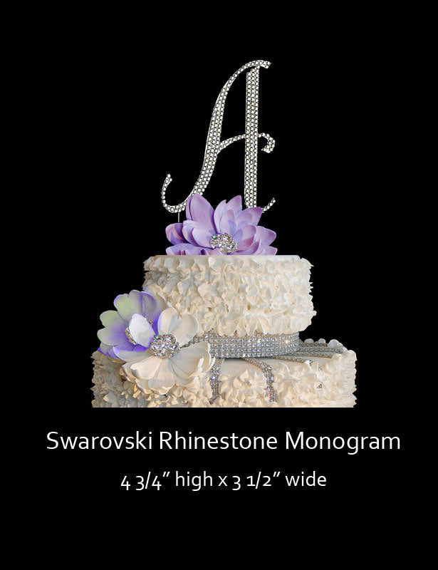 A full view of the Swarovski monogram cake topper sitting on top of a wedding cake.