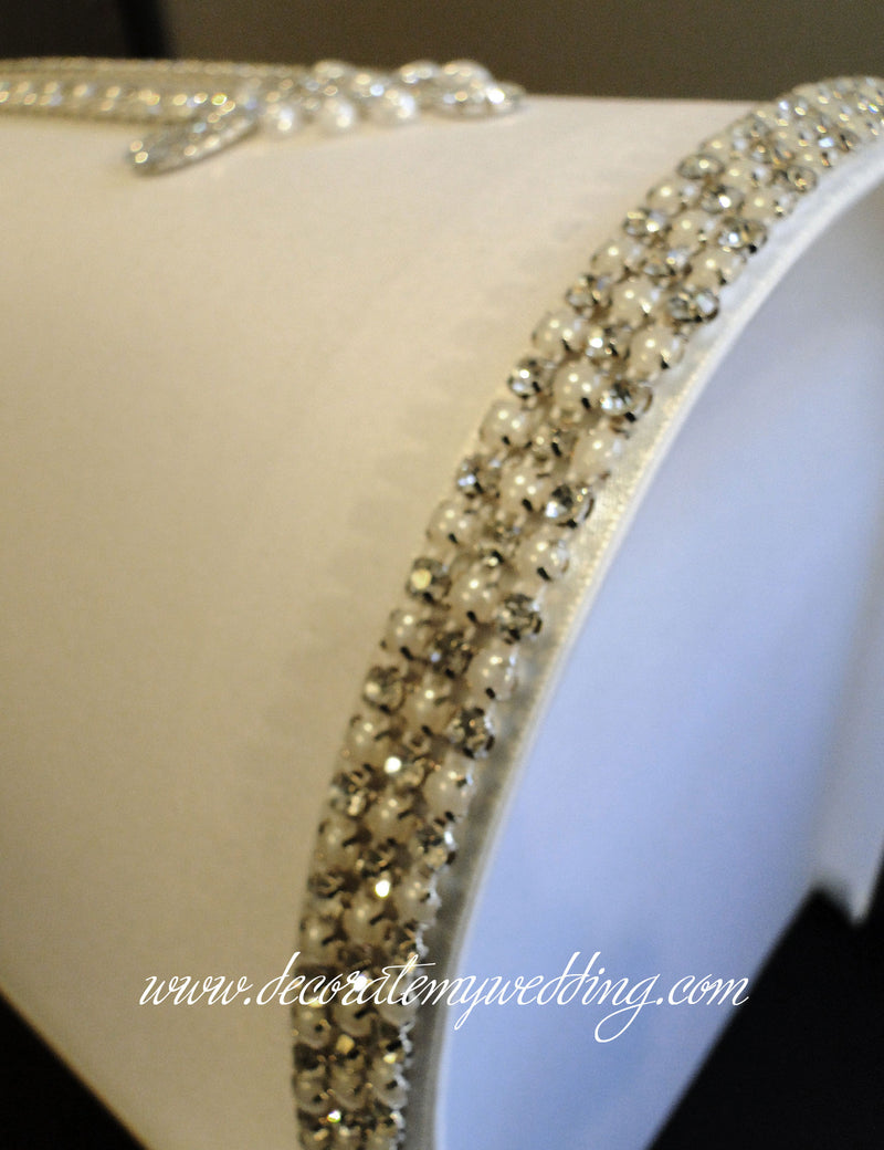 A close up at the pearl and rhinestone trim positioned on the curvature of the card box.