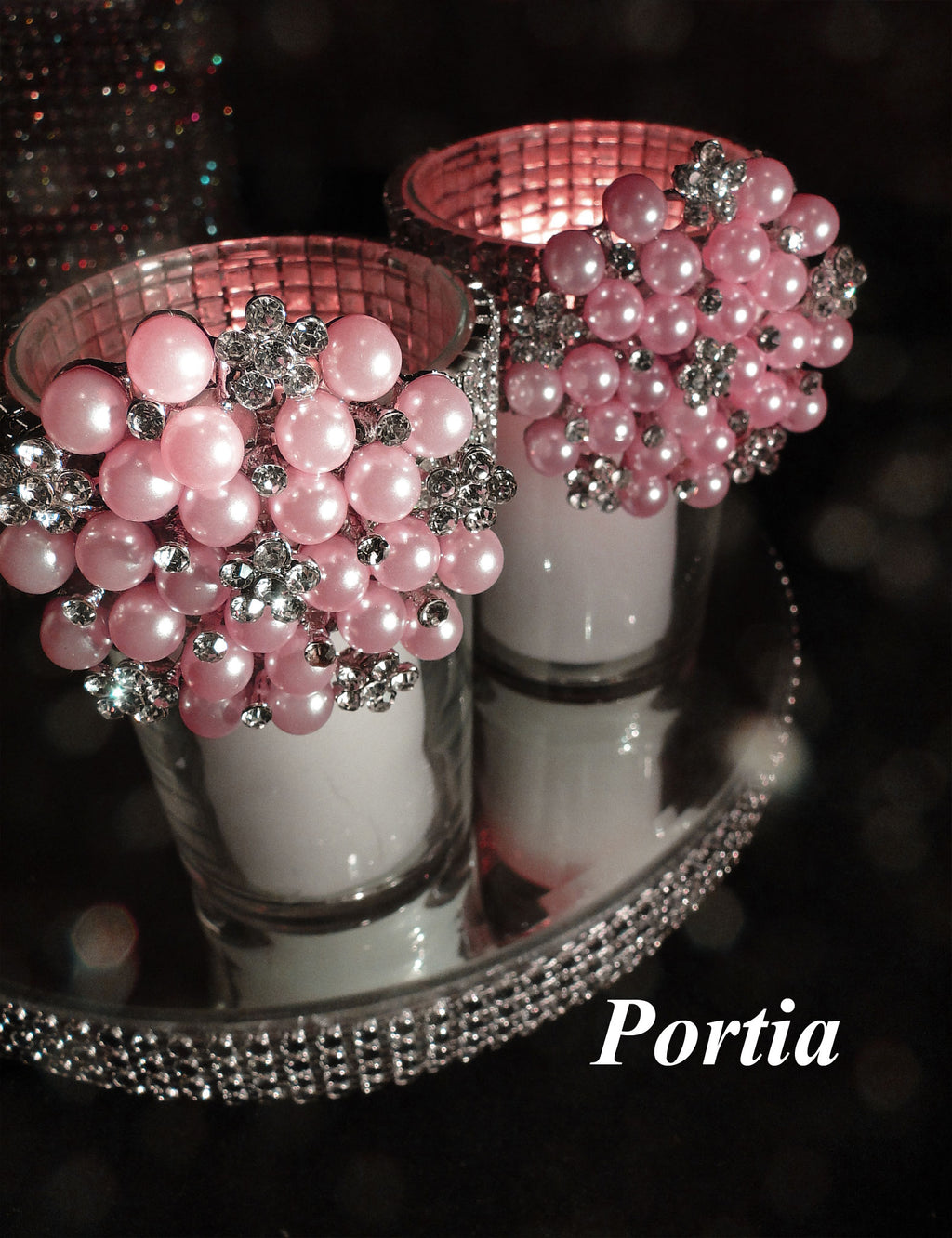 Two votive holders decorated with pink rhinestone brooches.
