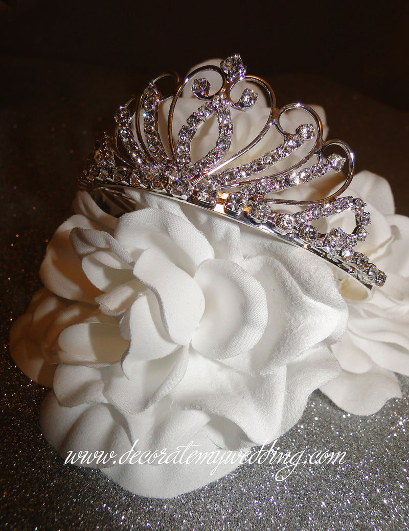 "This mini princess tiara is completely covered with clear glass rhinestones, and measures 1 ½"" high."