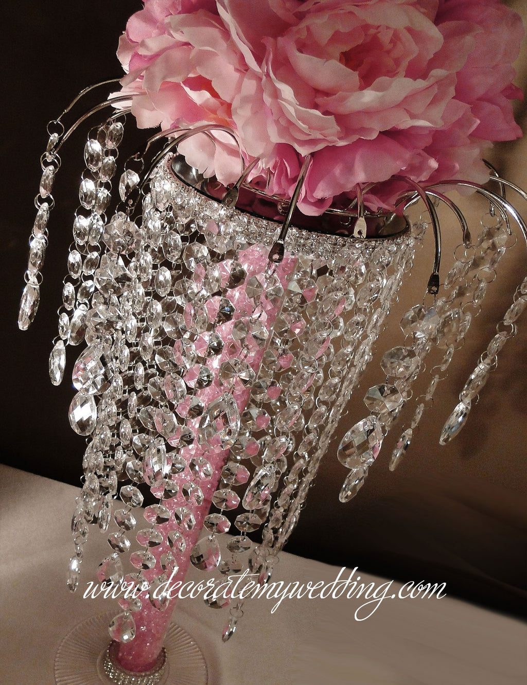This is a reception centerpiece that people will be talking about long after the wedding. Sparkling crystal beads dangle from a graceful arch with romantic pink accents.