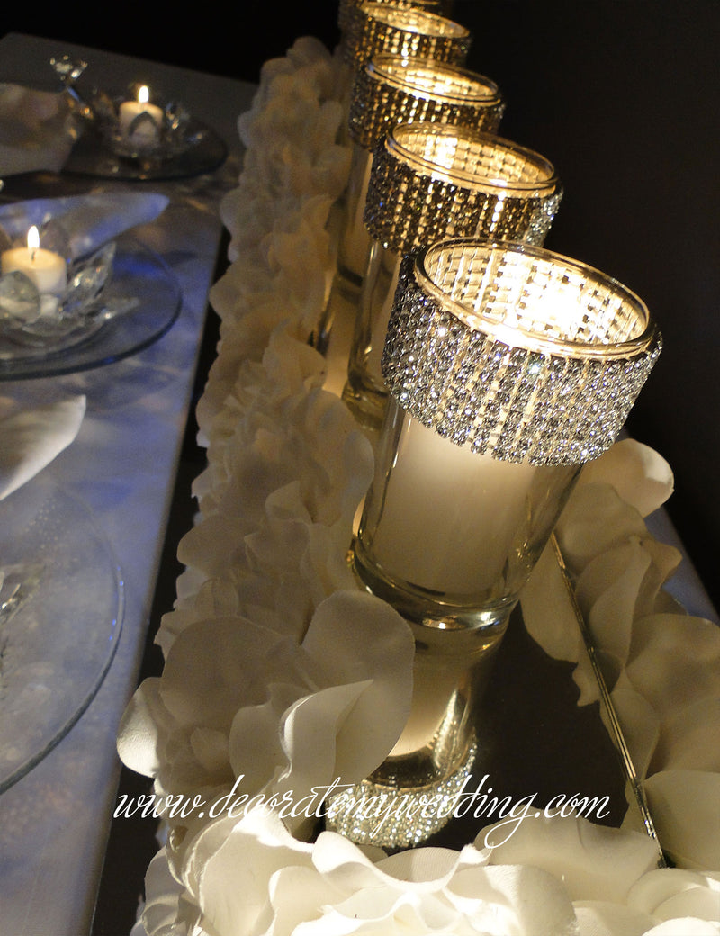 The votive candle flames that flicker inside the sparkling rhinestone candle holders create a romantic ambience on a wedding table.