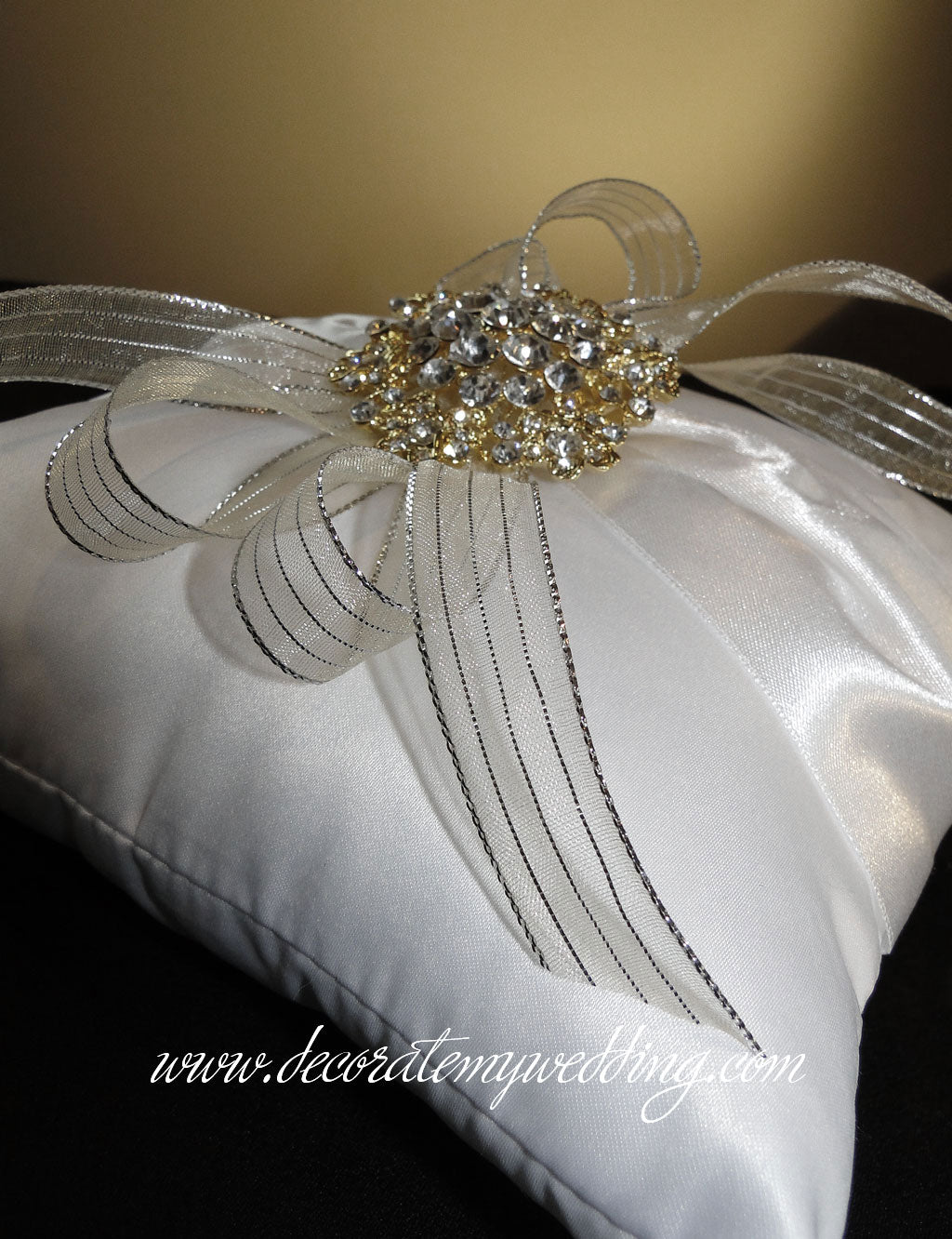 Ring bearer pillow trimmed with metallic gold ribbons and a rhinestone brooch.