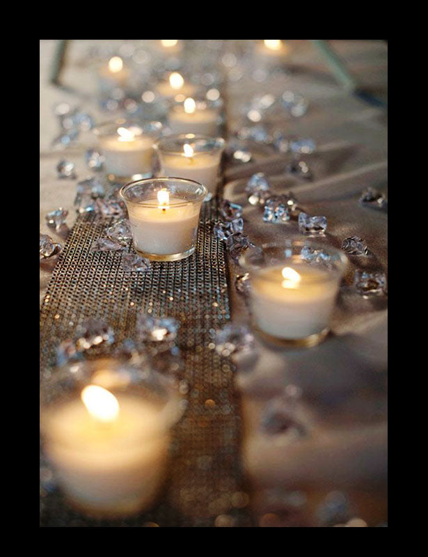 Scatter crystals are intermingled with votive candles on a wedding table.