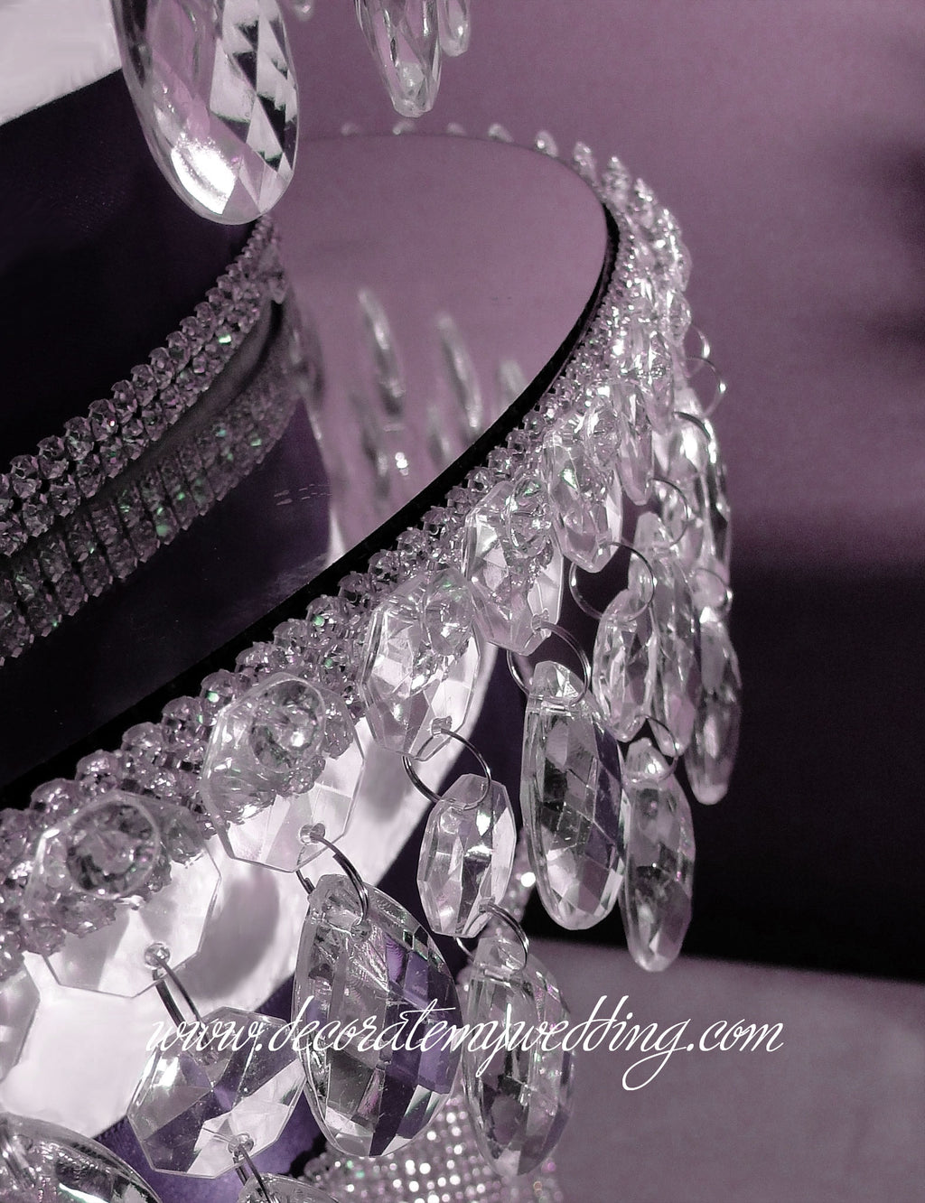 This cake separator is placed on top of a layer of cake to add a tier of dangling crystal beads and teardrop pendants.