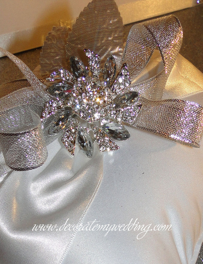 A close look at the white satin fabric and ribbons used to make the ring pillow.
