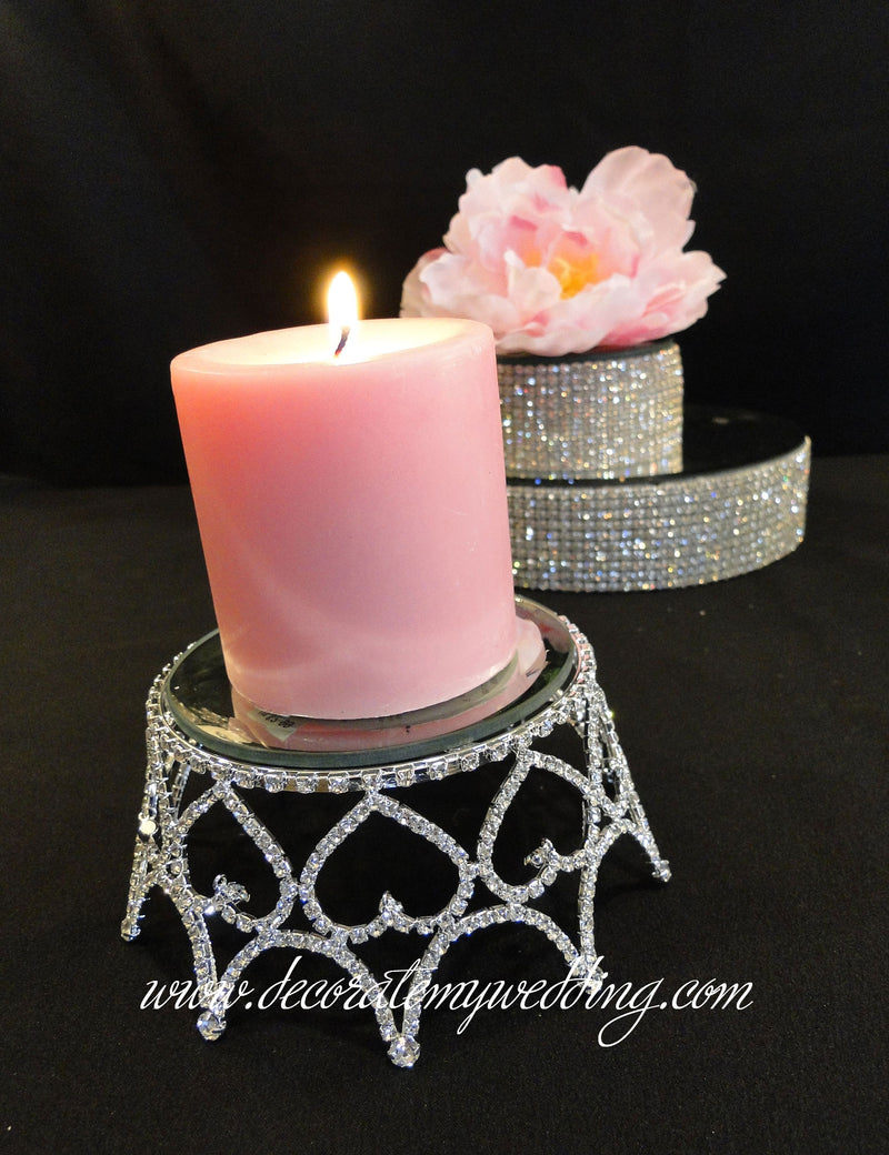 This table candle holder has a heart design, is completely covered with rhinestones, and holds a pillar candle.