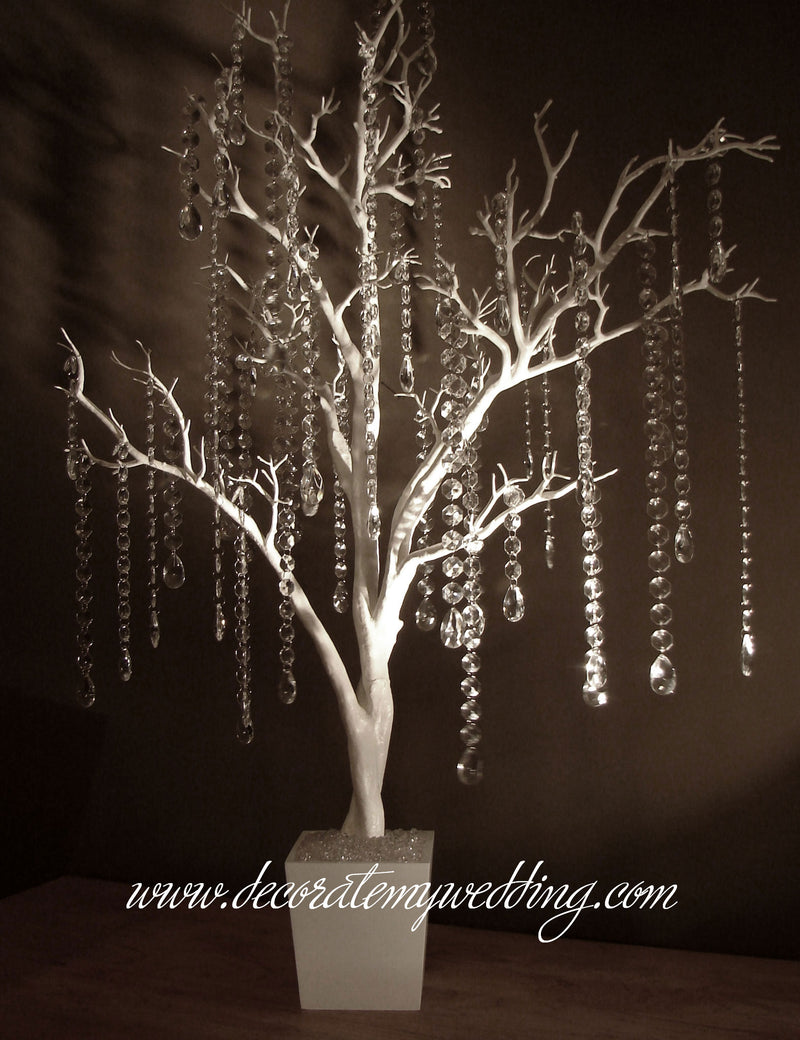A white tree with crystal link strands and teardrops creates a stunning tree centerpiece for your wedding reception.