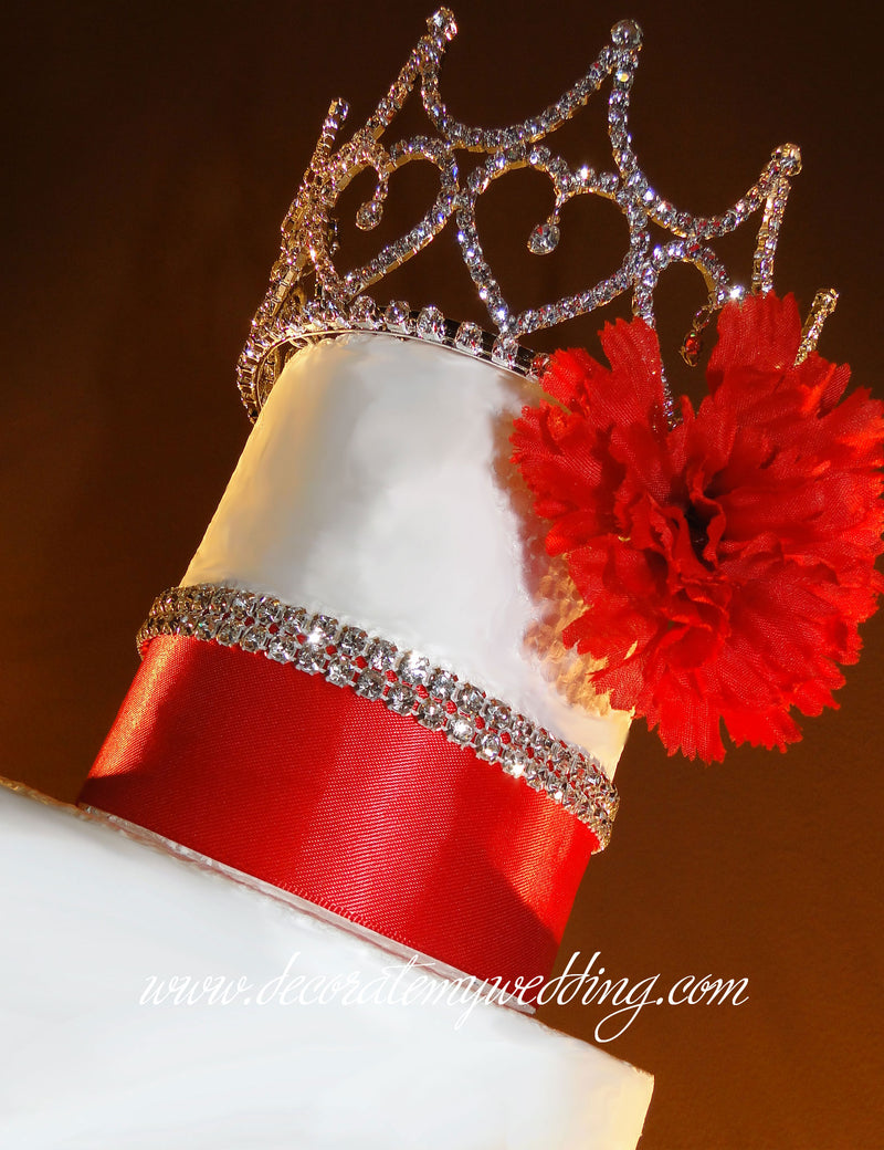 A upward look at the tiara crown positioned on the top of a wedding cake.