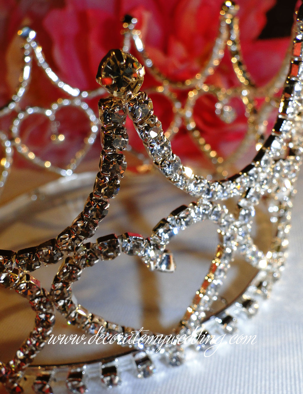 This tiara cake crown has a heart shaped design with a dangling tiny crystal heart in the center. Completely covered with clear Swarovski rhinestones.