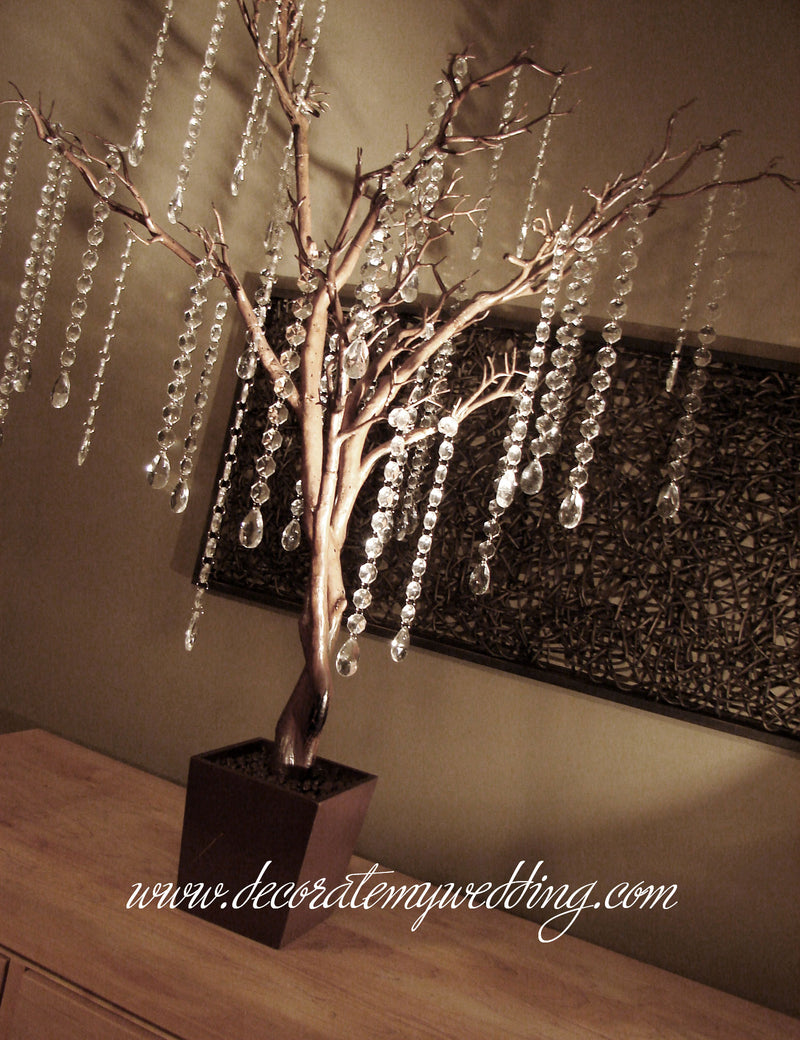 A brown tree with crystal link strands and teardrops creates a stunning tree centerpiece for your wedding reception.
