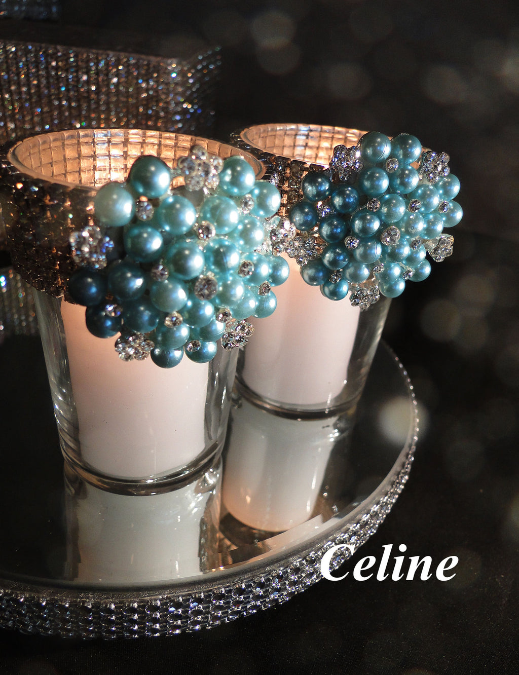 Two votive holders decorated with turquoise brooches and rhinestone banding.