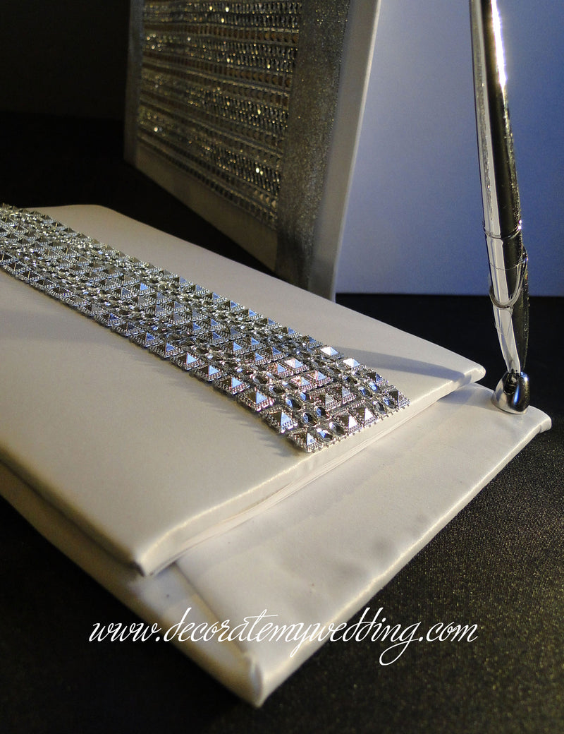 This unique wedding guest book has a strip of rhinestones and a silver pen attached to the book.