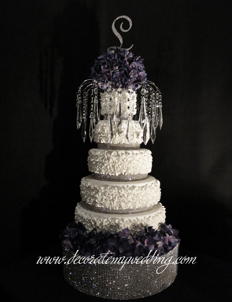 A full view of the diamond wedding cake topper sitting on top of a wedding cake.