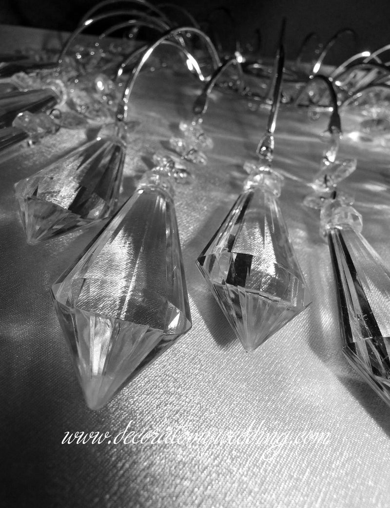 A close up look at the acrylic diamond pendants that hang from the wedding cake topper.