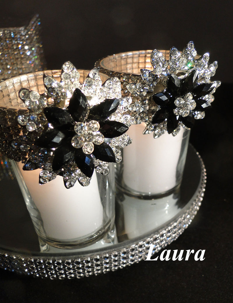 Two votive holders sitting on a rhinestone mirror decorated with black brooches.