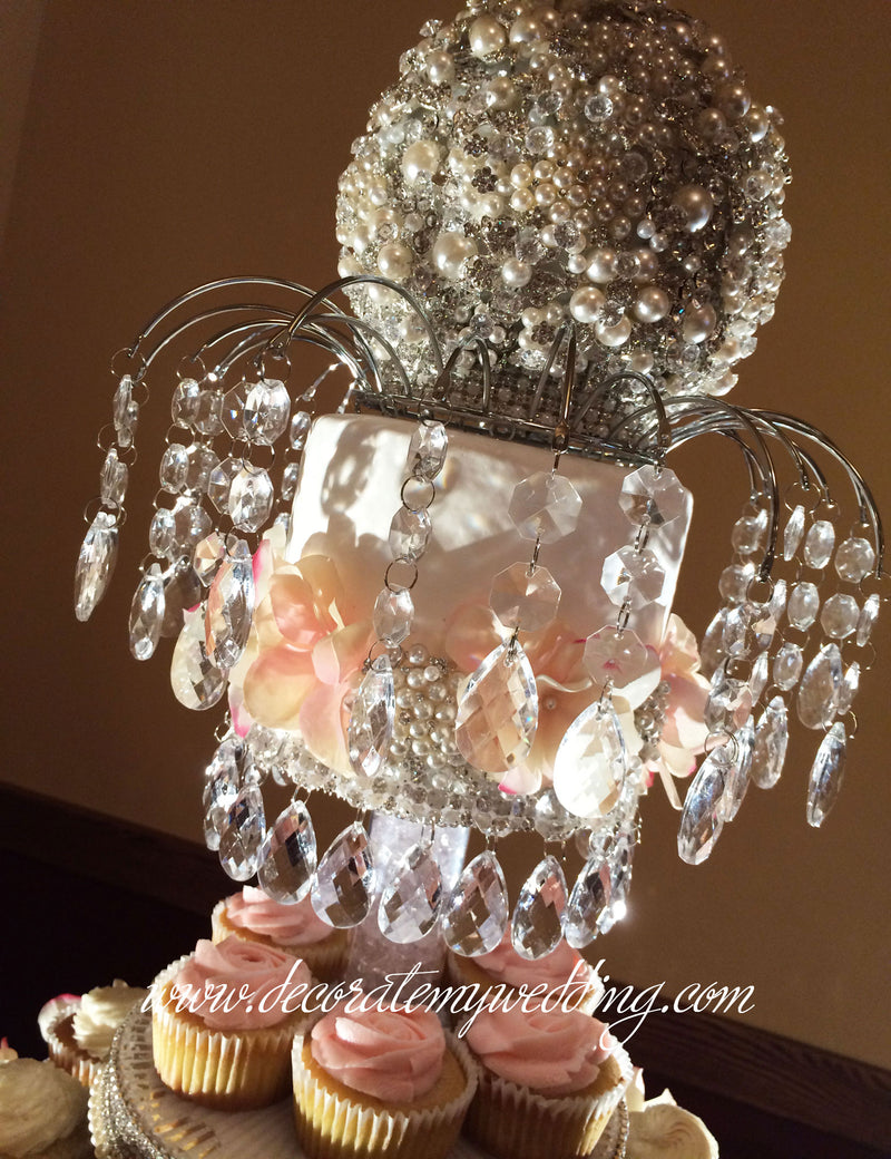 The arch with hanging crystal beads and the pearl brooch topper are included in the purchase.