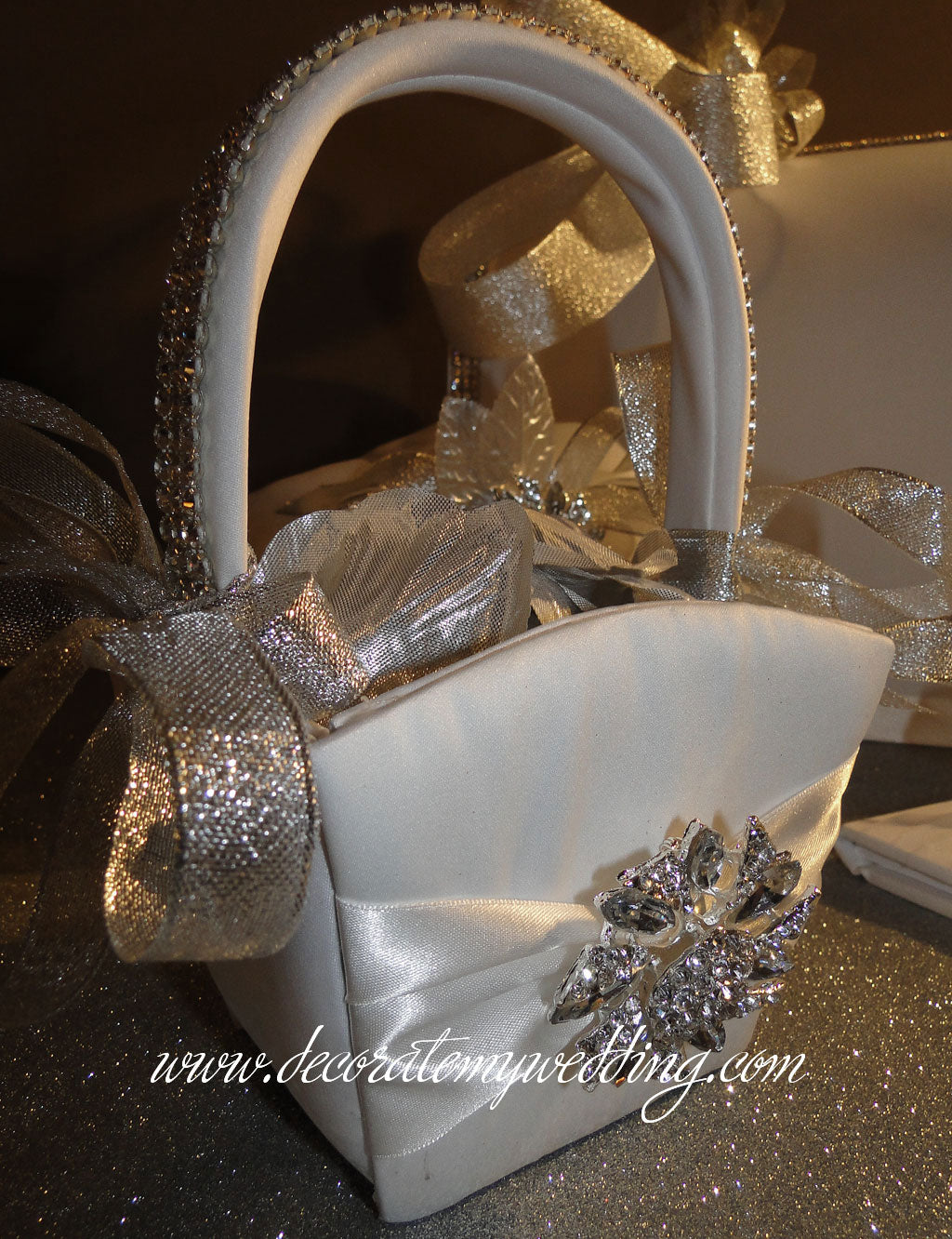 Wedding flower basket is trimmed with silver rhinestone banding, metallic ribbons, and a rhinestone brooch.
