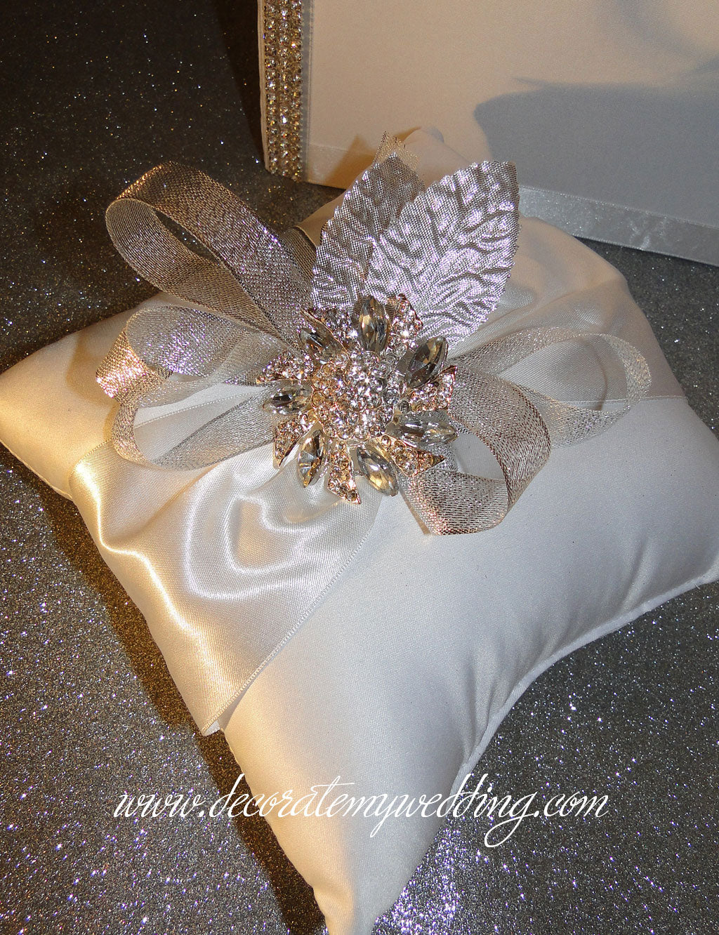 The wedding ring pillow is trimmed with silver ribbons and a clear rhinestone brooch.