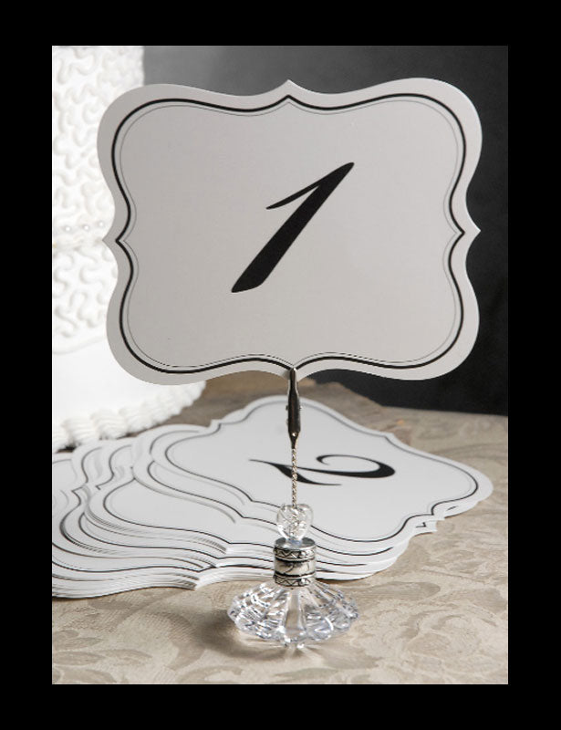 A crystal clear, perfume-bottle-shaped holder with a clip displays the wedding table number aiding wedding guests in locating their assigned table.