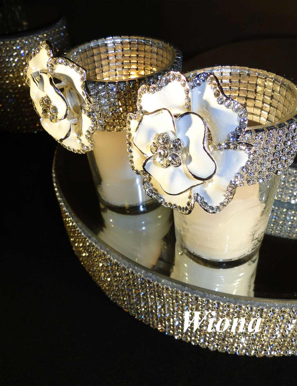 Two votive holders decorated with white brooches and silver rhinestone banding.