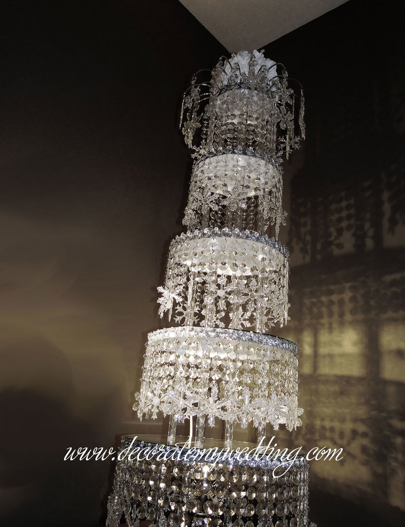 Stacks of crystal tiers with dangling snowflakes creates a spectacular winter wonderland centerpiece.