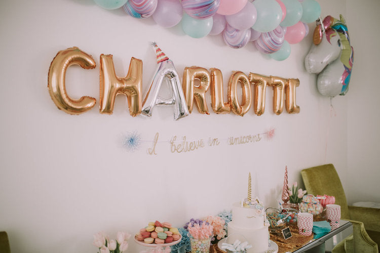 "Metallic mylar balloons spelling out ""Charlotte"" on the wall."