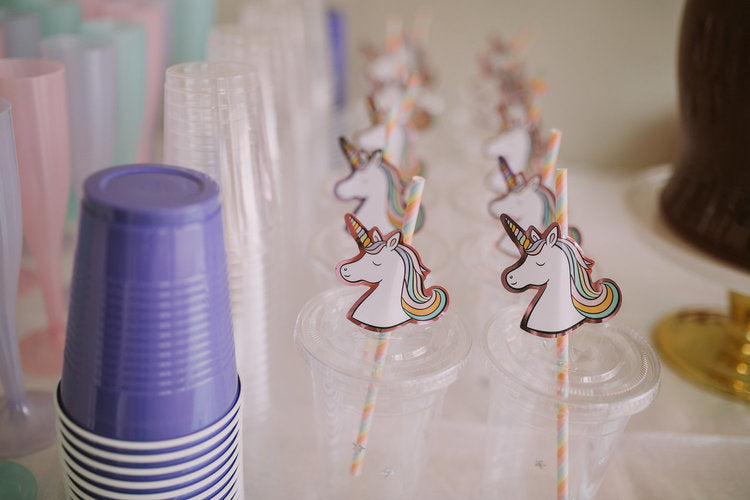 Closeup photo of plastic cups with unicorn paper straws