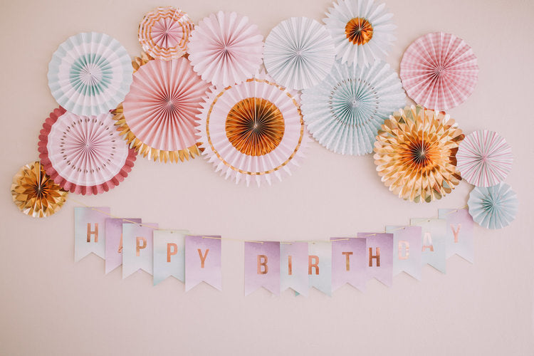 "Shot of wall with pastel pinwheel decorations over a ""Happy Birthday"" banner"