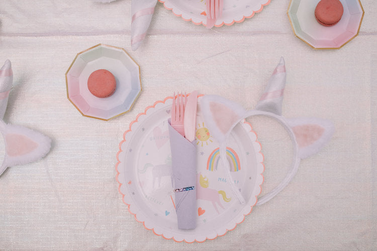 Overhead photo of individual table settling of paper plate, utensil, and unicorn headband