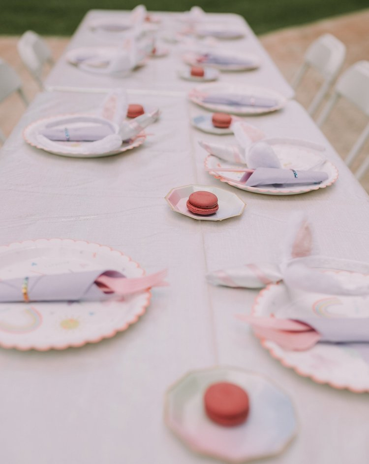 View of long table with party plates, utensils, and pink macarons