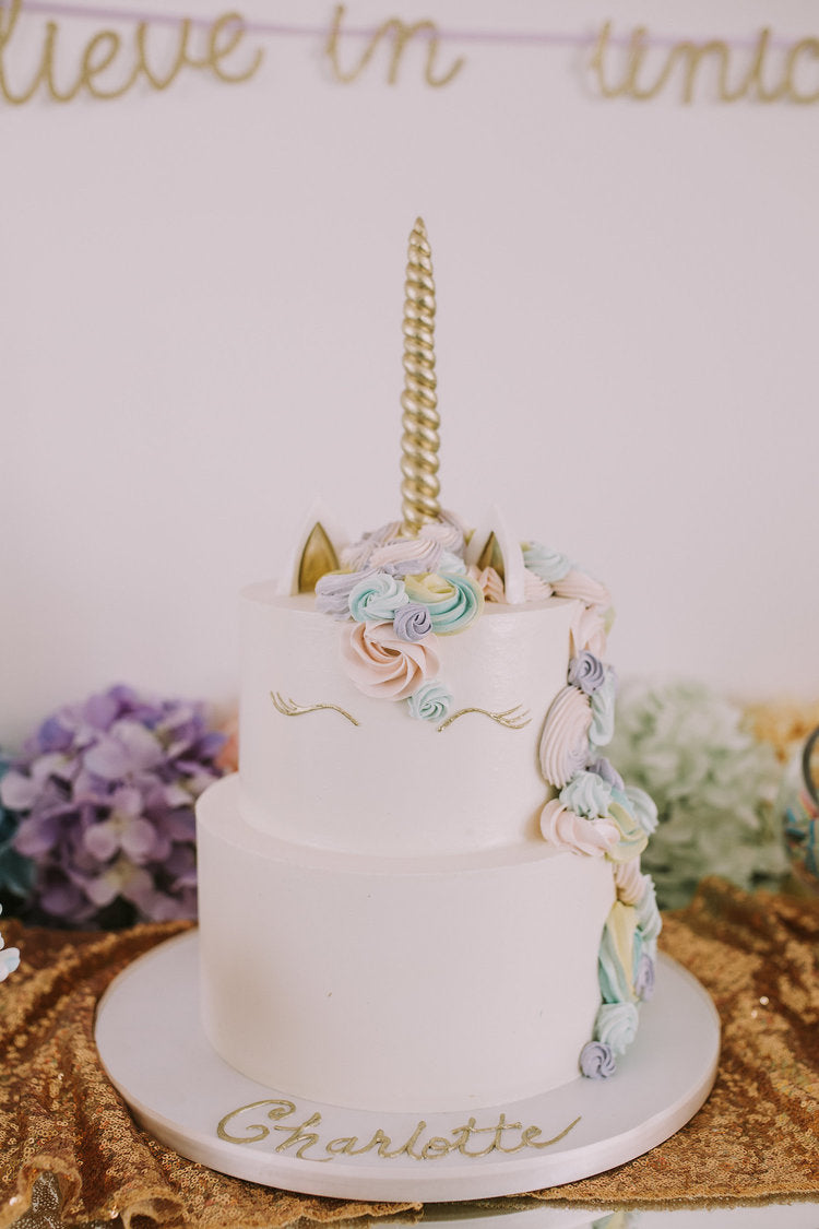 White unicorn themed cake on a decorated table