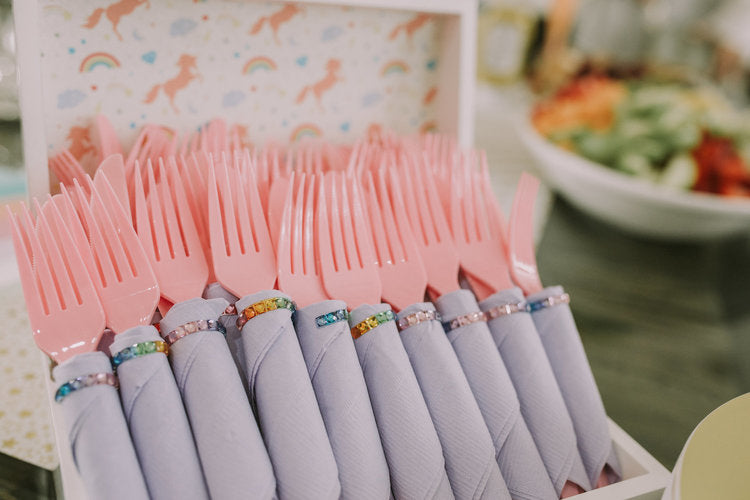 Box of pink forks with decorated napkins wrapped around each fork