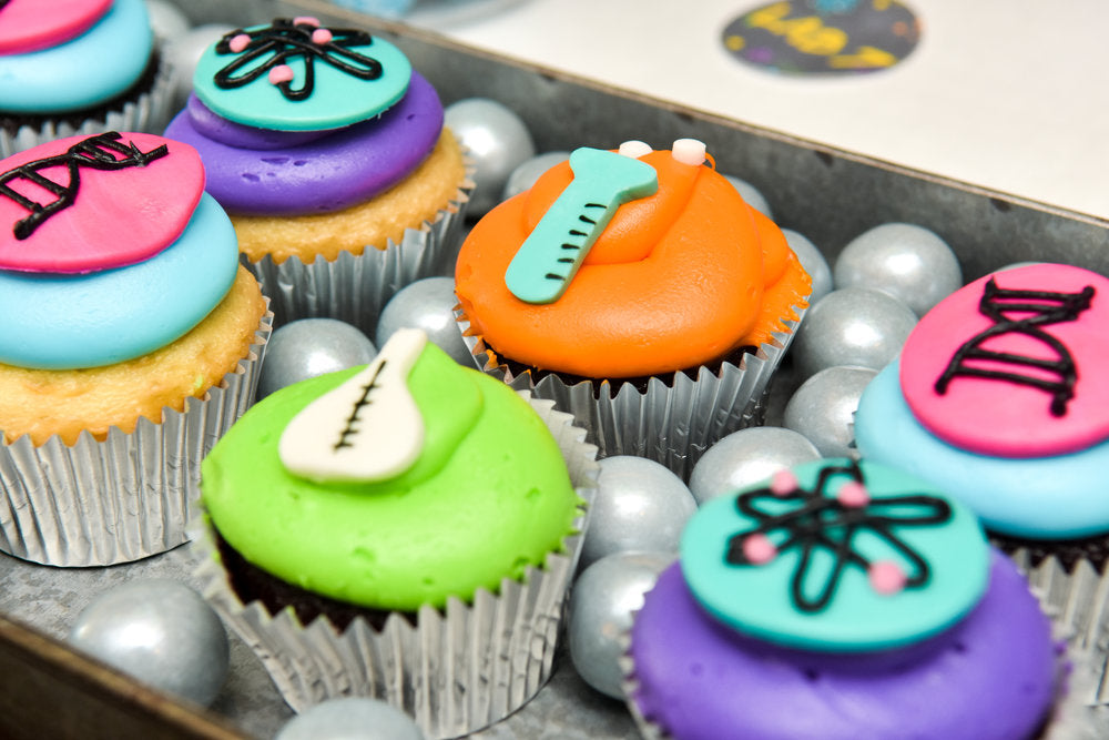 Closeup of cupcakes decorated with laboratory symbols