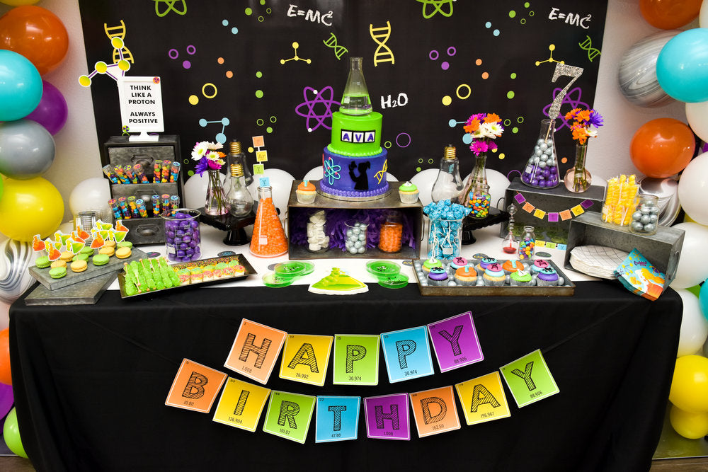 Table with science themed birthday cake, cookies, candies, and balloons