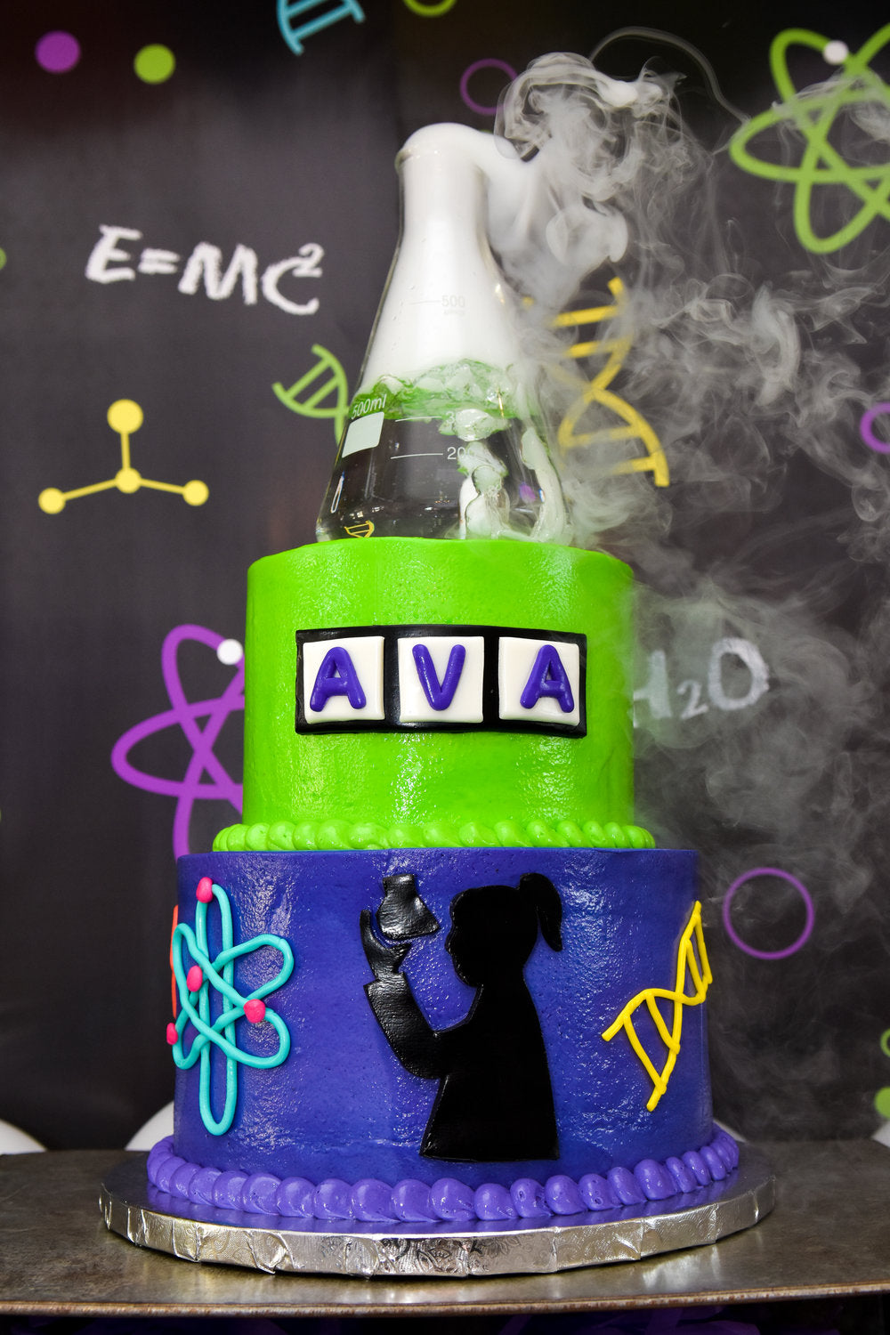 Closeup of purple & green birthday cake with smoking flask cake topper