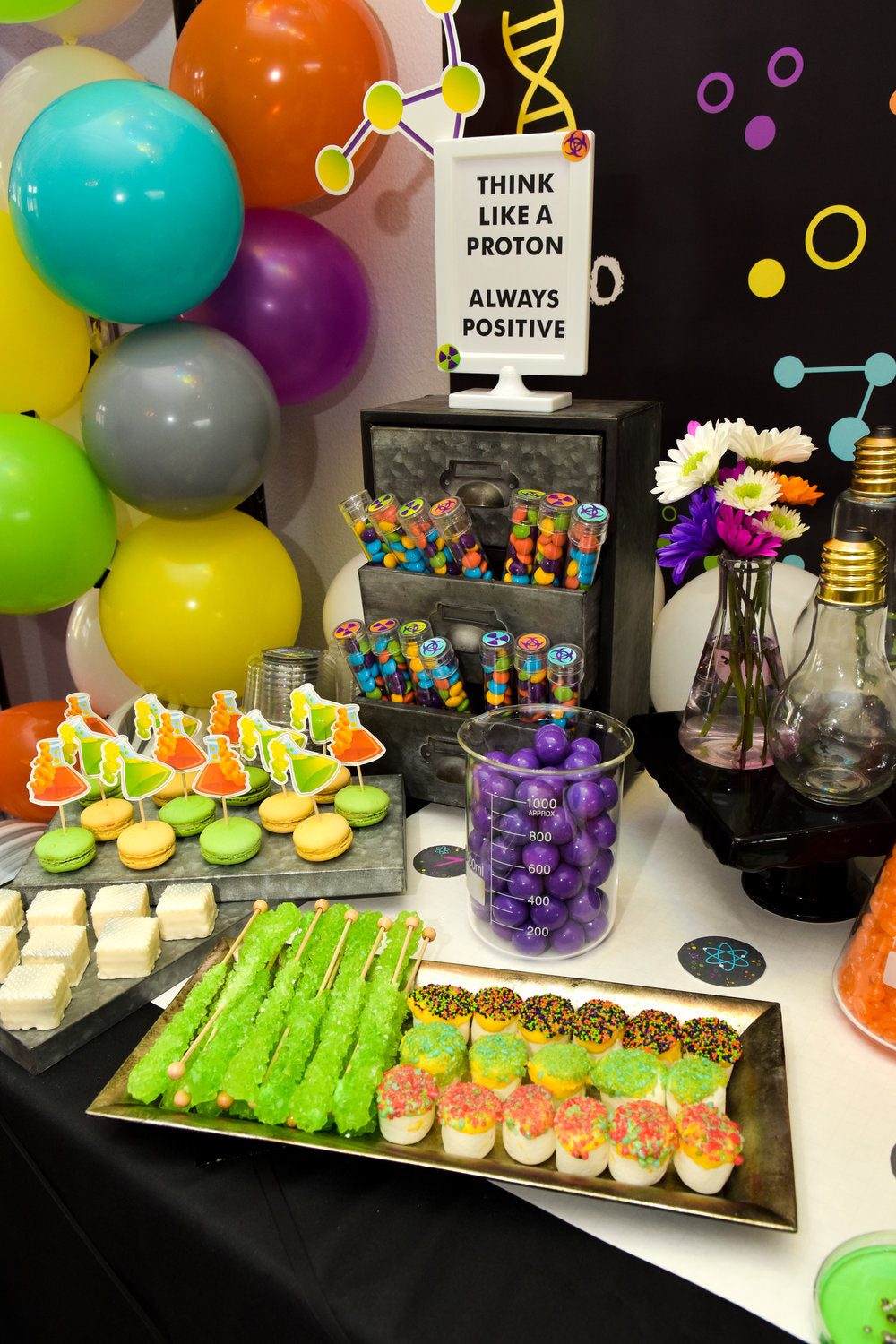 "Closeup of macaroons, candies, and a ""Think Like a Proton-Always Positive"" sign"