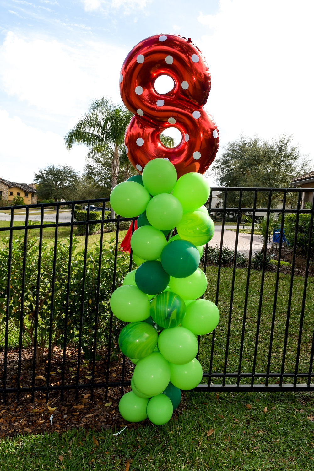 """8"" mylar balloon sitting on top of green balloons"