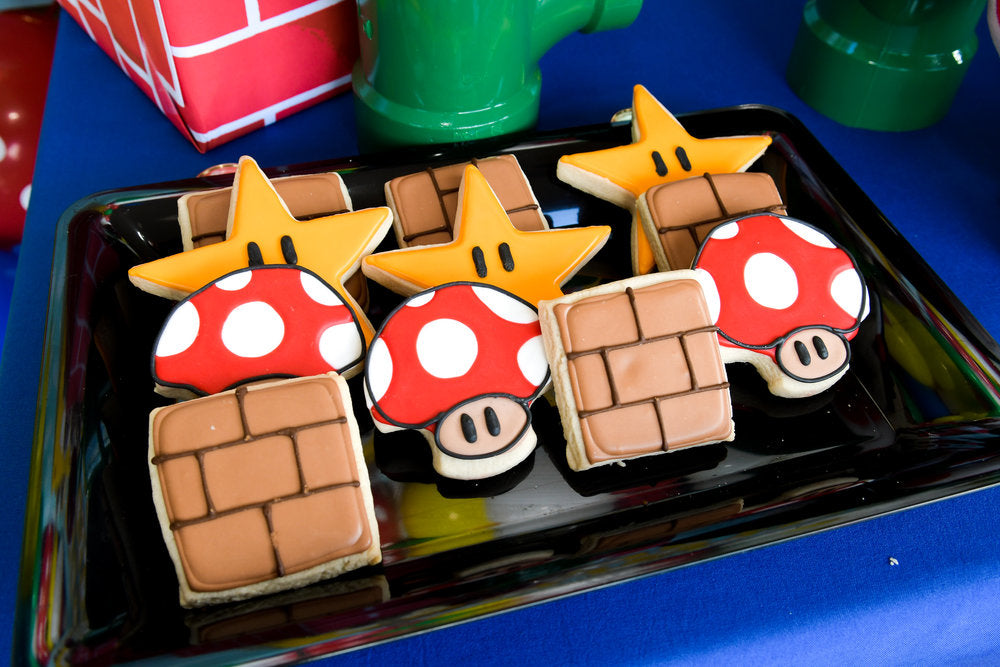 Closeup photo of Super Mario Bros star, brick, and mushroom decorated cookies